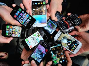 People show their smartphones on December 25, 2013 in Dinan, northwestern France. AFP PHOTO / PHILIPPE HUGUEN